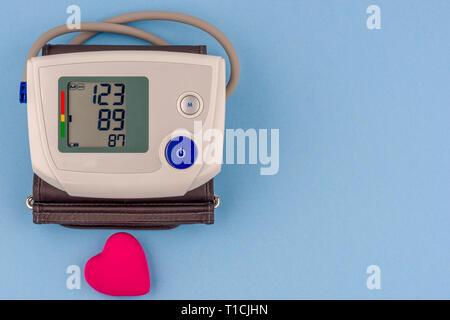 Moderne elektronische Blutdruckmessgerät mit roten Herzen auf einem blauen Hintergrund. - Stockfoto
