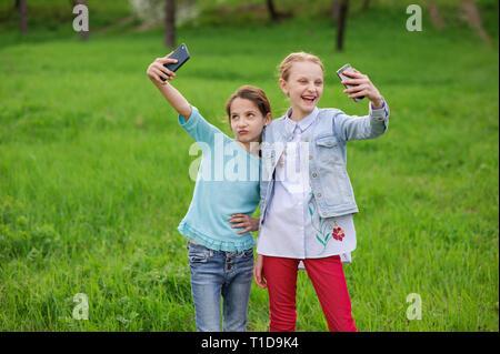 Gerne hübsche Mädchen mit Smartphones, selfie outdoor Spring Green Park - Stockfoto