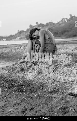 Schwarz-weiß Foto eines Mädchens in einem Kleid auf dem Boden sitzend. - Stockfoto