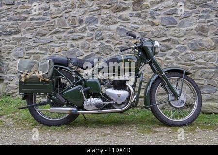 Klassische Triumph TRW 500 cc Militär Motorrad von einem Stein Wand auf einem Bauernhof in North Wales geparkt - Stockfoto