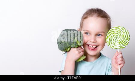 Wenig schöne Mädchen Spaß haben mit Brokkoli und Lutscher. Wählt, was besser zu essen - Stockfoto