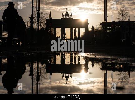 Berlin, Deutschland. 25 Mär, 2019. Die Sonne hinter dem Brandenburger Tor, das in einer Pfütze widerspiegelt. Credit: Paul Zinken/dpa/Alamy leben Nachrichten - Stockfoto