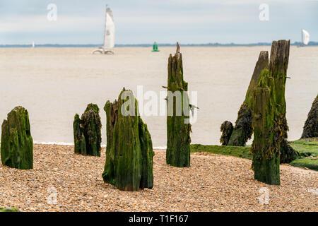 Stützstange auf einem Kieselstrand mit Booten in den unscharfen Hintergrund, am Hafen von Felixstowe, Suffolk, England, UK gesehen - Stockfoto