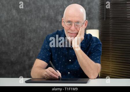 Ein Senior Designer über Grafik Tablett im Büro - Stockfoto