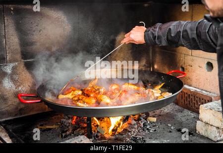Kochen und eine traditionelle spanische Paella über offenem Feuer. Die traditionelle Art der Vorbereitung valencianische Paella mit Feuer und Flamme in einem großen Topf. - Stockfoto