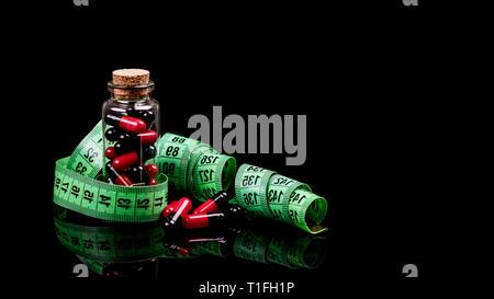Nahaufnahme einer Glasflasche mit Diätpillen und Maßband auf schwarzem Hintergrund isoliert. - Bild - Stockfoto