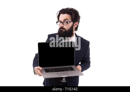 Stirnrunzelnd bärtigen Geschäftsmann mit einem Laptop in der Hand und hob eine Augenbraue in die Kamera schaut, auf weißem Hintergrund - Stockfoto