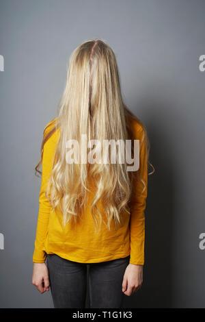 Schüchterne junge Frau mit verdeckt Gesicht hinter langen blonden Haare - deprimiert oder emabarrassed oder gleichgültig Jugendmädchen - Stockfoto