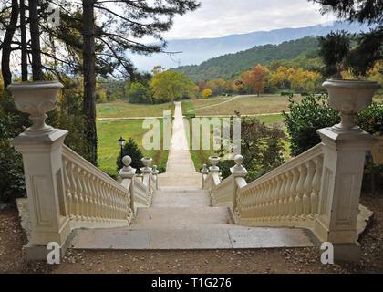 Ein weißer Stein Treppe im Herbst Garten führt an die gelbe Bäume im Herbst auf einem Hintergrund der Berge mit Herbst Wolken - Stockfoto