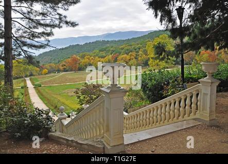 Ein weißer Stein Treppe im Herbst Garten führt an die gelbe Bäume im Herbst auf einem Hintergrund der Berge mit Herbst Wolken