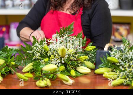 Frau florist tragen Schürze stehen an der Theke, Blumenstrauß für Client im Flower Shop.