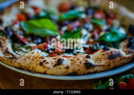 Authentische italienische neapolitanischen Stil Holzofen Pizza auf der Tabelle in einer Pizzeria Trattoria Restaurant. Selektiver Fokus auf Kruste - Stockfoto