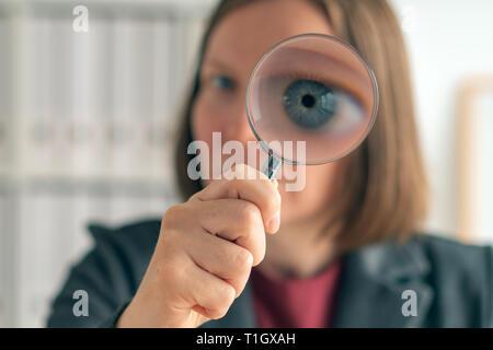 Geschäftsfrau mit Lupe, die finanzielle Überwachung, Prüfung und Bewertung von Jahresabschlüssen. - Stockfoto