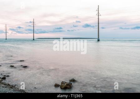 Sonnenuntergang in Islamorada, Florida Keys mit Rosa himmel felsen Stromleitungen auf felsigen Strand lange Belichtung glatte blurry transparent grün seichte Wasser am Golf - Stockfoto