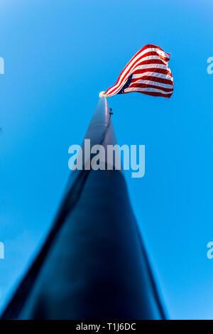 Auf der Suche nach einem Fahnenmast in Richtung der amerikanischen Flagge, Sterne und Streifen, winken in den Wind, gegen einen schönen blauen Himmel an einem sonnigen Sommertag - Stockfoto