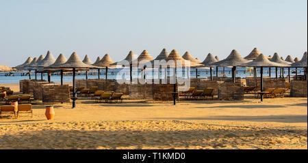 Reihen von Sonnenschirmen und Sonnenliegen am Strand. - Stockfoto