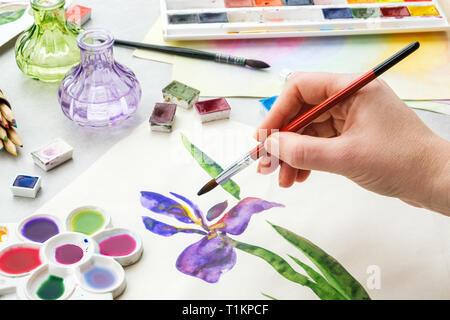 Maler mit einem Pinsel in der Hand. Aquarell Zeichnung - Iris Blume und künstlerische Ausstattung auf dem Schreibtisch. Ansicht von oben. Maler Zeichnung am Arbeitsplatz. - Stockfoto
