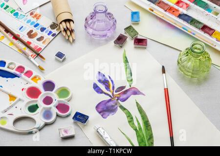 Aquarell Zeichnung - Iris Blume - und künstlerische Ausstattung auf dem Schreibtisch. Ansicht von oben. - Stockfoto