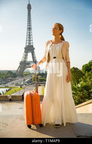 Schöne Frau in langen Kleid mit orangefarbenen Koffer stehen auf Trocadero Platz. Paris Stadtbild, Blick auf den Eiffelturm. Travel Concept - Stockfoto