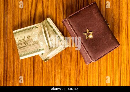 Indische fünfhundert (500) Rupie Geldschein in brauner Farbe Brieftasche Leder Geldbörse auf einem Holztisch. Wirtschaft Finanzen Wirtschaft Konzept. Hohe Engel Anzeigen wit - Stockfoto