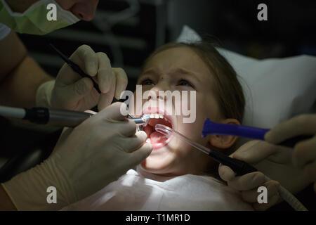 Angst kleines Mädchen im Zahnarztbüro, Schmerzen während einer Behandlung. Kinder Zahnpflege und Angst vor dem Zahnarzt. - Stockfoto