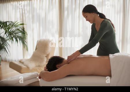 Weibliche Masseurin, Mann, Massage - Stockfoto