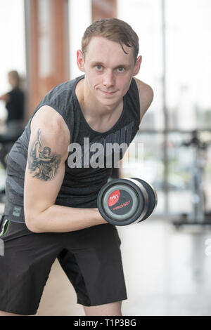 Ein junger Mann hebt Gewichte in einer Turnhalle UK - Stockfoto