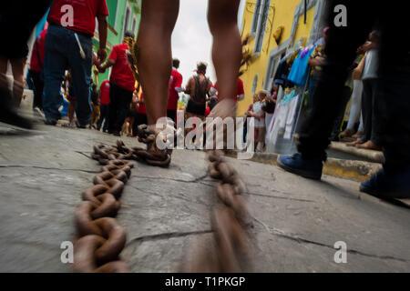 Eine katholische Pönitenten zieht Ketten, an seinen Beinen befestigt, während der Heiligen Woche Prozession in Atlixco, Mexiko. - Stockfoto