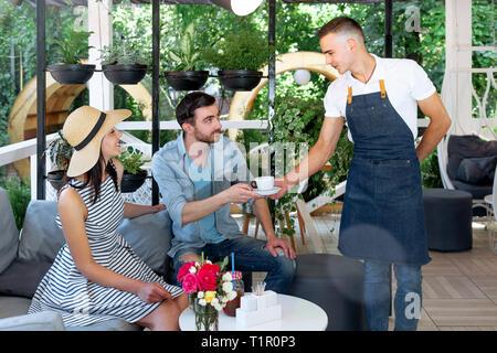 Eine nette junge Kellner in einem weißen T-Shirt und eine blaue Schürze mit einer Tasse Kaffee in der Hand. Portrait von selbstbewussten jungen männlichen barista Kaffee - Stockfoto