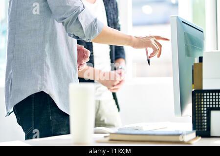 Asiatische Führungskräfte stehen vor der Diskussion von Plänen in modernen Büro. - Stockfoto