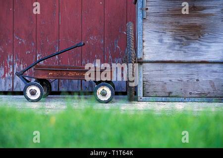 Rusty Radio Flyer Red Wagon außerhalb einer Vermont Scheune - Stockfoto