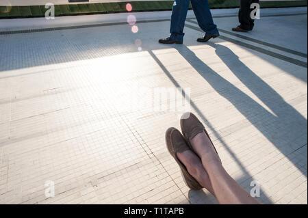 Eine Frau entspannt sich in der Abendsonne, während Passanten lange Schatten werfen. - Stockfoto