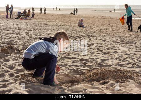 Einem jungen kaukasischen Jungen graben ein Loch in den Sand bei Formby Strand, Merseyside, UK. - Stockfoto