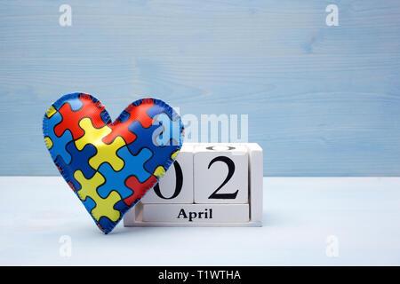 Welt Autismus Bewußtsein Tag, psychische Gesundheit Konzept mit Jigsaw puzzle oder Muster auf Herz mit Kalender auf Blau, Holz- Hintergrund - Stockfoto