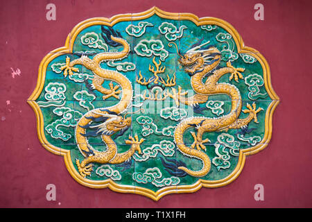 Zwei Drachen glasierte Fliesen- auf eine Rote Wand in Peking. Drachen sind wichtig in der buddhistischen kunst und Mythen - Stockfoto