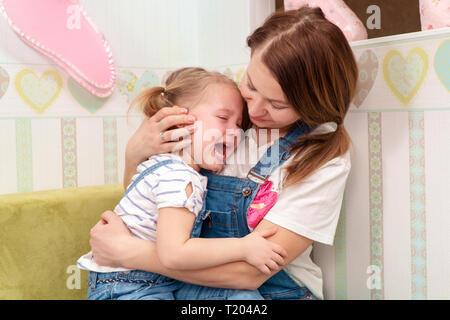 Mutter umarmt weinend Tochter auf dem Arm sitzen - Stockfoto
