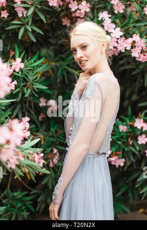 Herrliche Braut in schöne Hochzeit Kleid auf natürliche Hintergrund. Die atemberaubende junge Braut ist unglaublich glücklich. Hochzeitstag. Schönen Blumenstrauß - Stockfoto