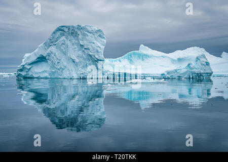 Ein erstaunlicher Eisberg auf dem Eisgraveyard in der Antarktis, der in einem Tierkreis eine schöne Reflexion an der Wasseroberfläche hervorruft