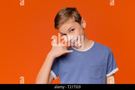Kommunikationskonzept. Flirty Junge, nennen mich Geste, in die Kamera lächeln, orange Hintergrund mit freier Speicherplatz - Stockfoto
