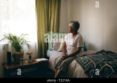 Ältere Frau auf dem Bett in den Ruhestand nach Hause sitzen - Stockfoto
