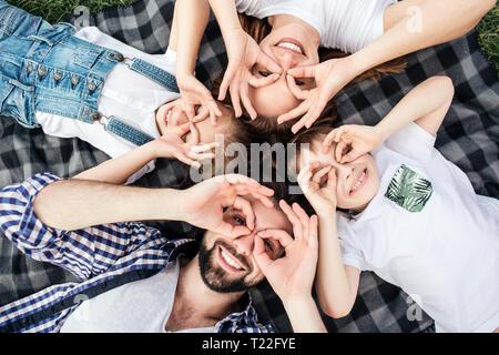 Lustiges Bild von Familie tun lustige Runden mit den Fingern auf die Augen. Sie spielen. Alle von ihnen liegen auf Decke und lächelnd. Sie sehen glücklich - Stockfoto