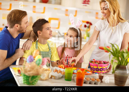 Lächelnde Frau mit Familie vorbereiten Ostern Korb mit bunten Eiern - Stockfoto