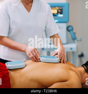 Magnettherapie. Physiotherapeuten Platzierung von Magneten auf Patienten zurück. - Stockfoto