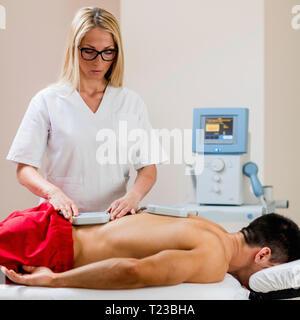 Magnettherapie. Physiotherapeuten Platzierung von Magneten auf Patienten zurück.