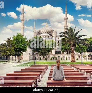 Frau auf der Bank mit Blick auf die Blaue Moschee in Istanbul, Türkei - Stockfoto