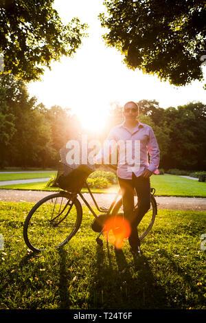 Mann stand in der Nähe von Fahrrad mit Picknick im Park - Stockfoto