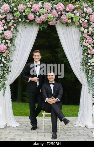 Paar der hübscher junger Männer in weißen Hemden und in der stilvollen schwarzen Anzug mit Fliege, lächelnd und unter den rosa blumenmuster Arch posieren. - Stockfoto