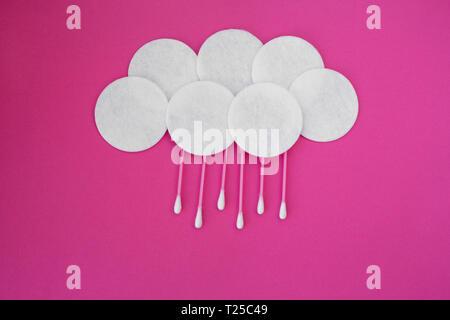 Draufsicht auf rosa Wattestäbchen mit weißen Kopf und Weiße runde Baumwolle Festplatten in Wolken mit Regen fällt auf einem rosa Hintergrund gelegt. - Stockfoto