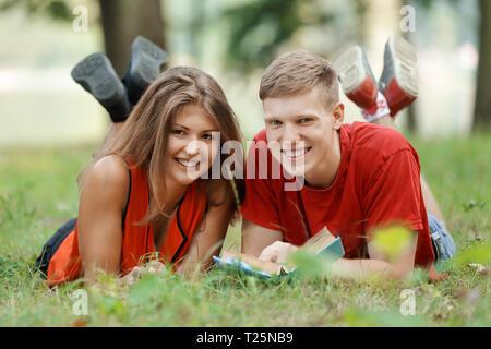 Paar Studenten, die auf dem Gras in den Park und ein Buch lesen - Stockfoto
