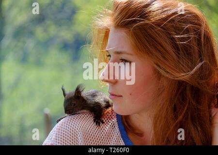 Portrait von rothaarigen Mädchen im Teenageralter mit Eichhörnchen auf der Schulter - Stockfoto